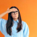 Chica con gafas tocándose la frente